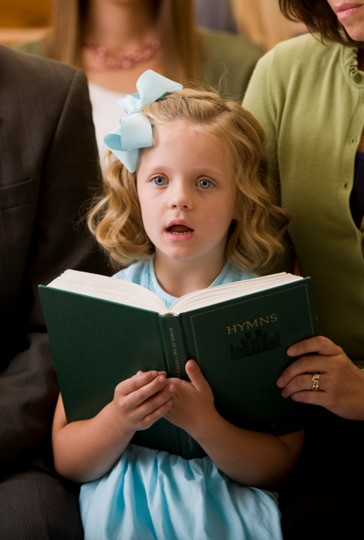 Young girl singing while holding an open hymnbook