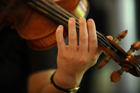 Close-up of a violinist, showing left arm, hand, and top half of the violin