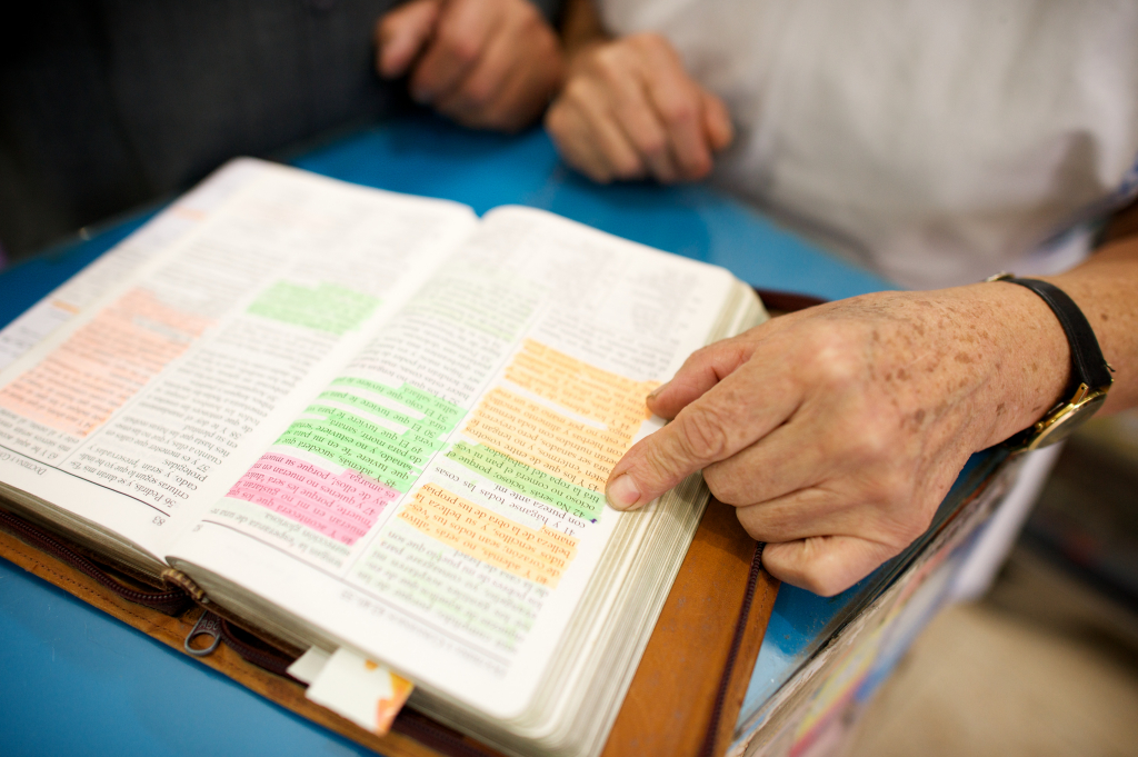 Photo of an older person reading from highlighted scriptures, showing only the hands and torso of the person