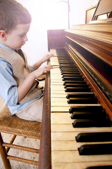 Young boy playing playing piano