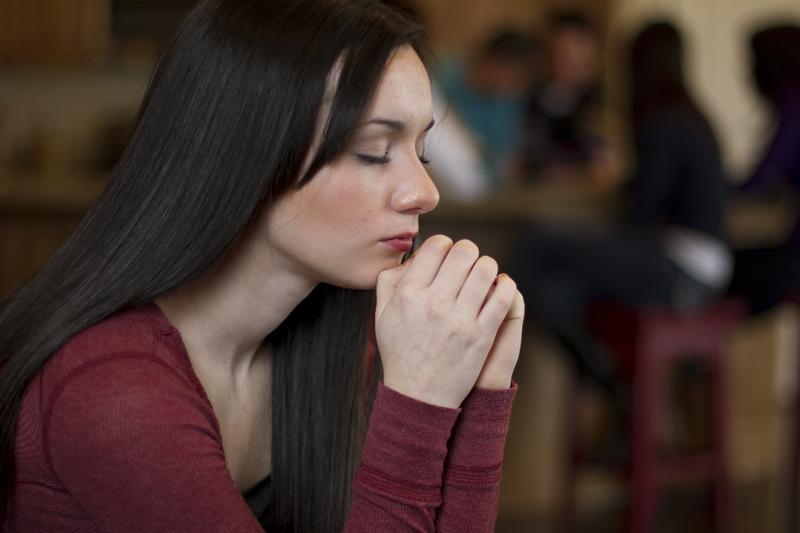 Teenage girl kneeling in prayer
